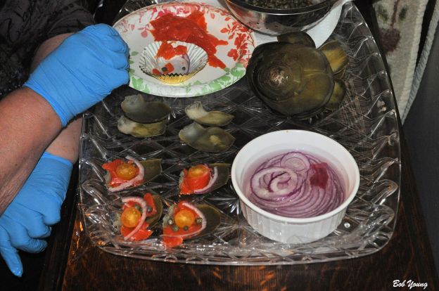 "Robin is assembling her Lox Canapes. (Lox, Tomato, Caper, Red Onion all on an Artichoke Leaf.)  Another  ""Yummer""."